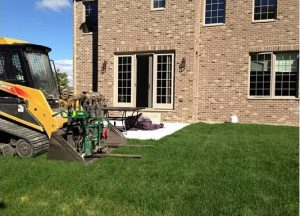 backhoe on a lawn outside of a brick house