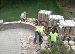 Workers building a large stone patio
