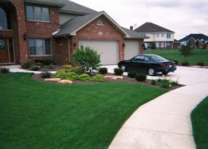 large lawn with flowerbed in front of a brick house
