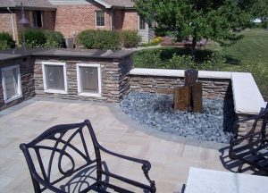 outdoor living bbq and dining space with water feature
