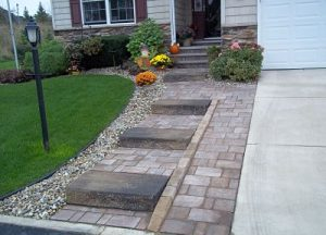 paver walkway next to driveway leading to front door