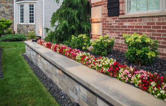 Retaining wall designed with rock border, and flowerbed