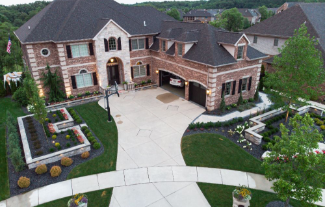 Overhead shot of large home with paver driveway with sidewalk