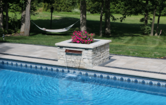 Poolwater feature next to pool, with flowers and small waterfall into pool