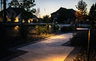 Paver pathway with flower beds lit with outdoor lighting design