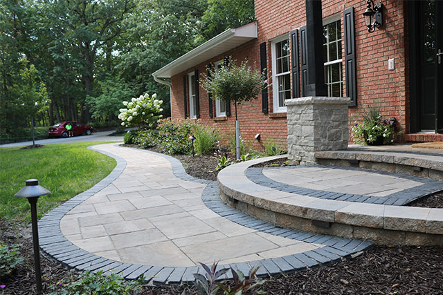 Paver entry walkway in front of brick house